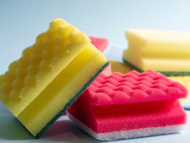 Vue latérale du nettoyage des éponges de différentes couleurs et tailles disposées sur un fond bleu. produits de nettoyage à domicile.
