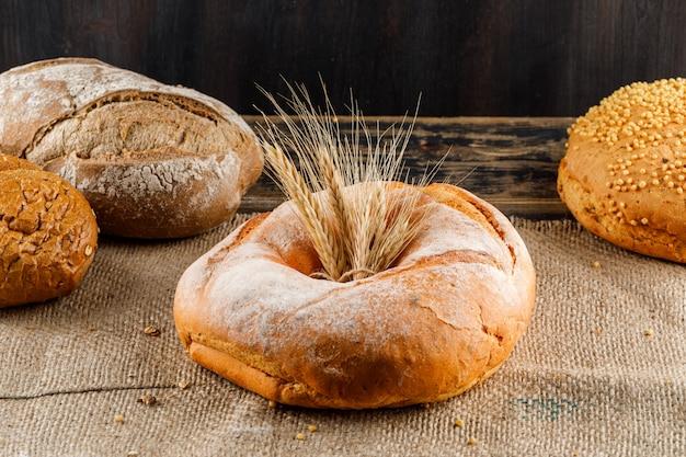 Vue latérale du pain avec de l'orge sur la surface texturée du sac. horizontal