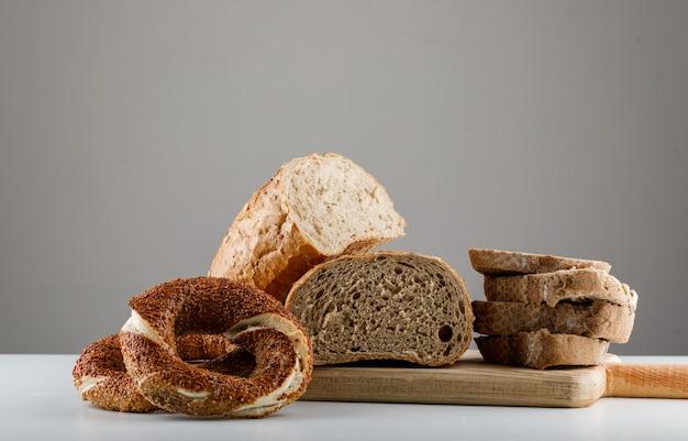 Vue latérale du pain en tranches sur une planche à découper avec bagel turc sur tableau blanc et surface grise. espace horizontal pour le texte