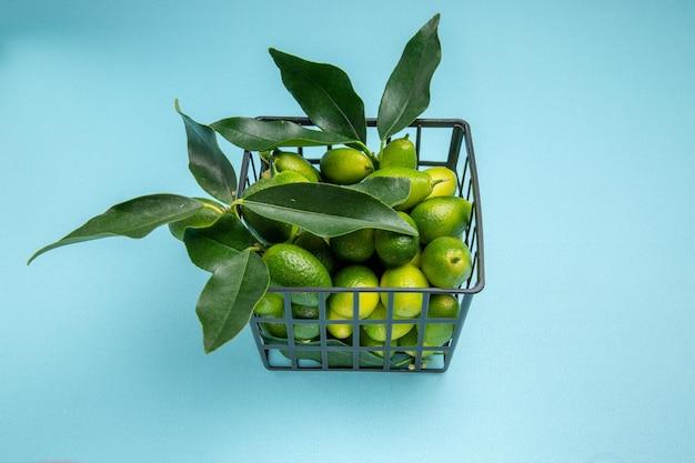 Vue latérale du panier gris d'agrumes avec des agrumes verts et des feuilles sur la table bleue