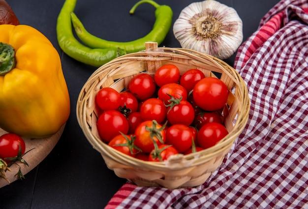 Vue latérale du panier de tomates sur tissu à carreaux avec bulbe de poivre et d'ail sur une surface noire