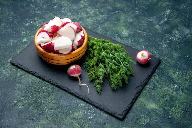 Vue latérale du paquet d'aneth frais et couteau de radis entiers sur une planche à découper noire sur fond de couleurs de mélange noir vert avec espace libre