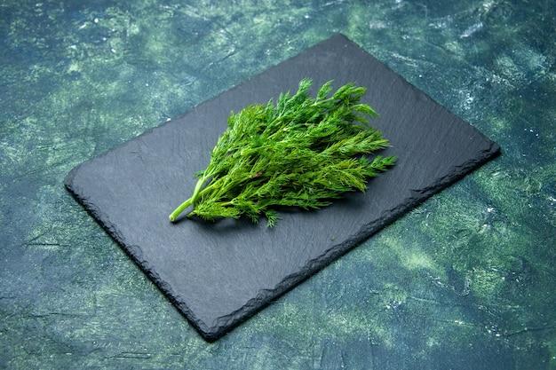 Vue latérale du paquet d'aneth frais sur une planche à découper noire sur fond de couleurs de mélange noir vert avec espace libre