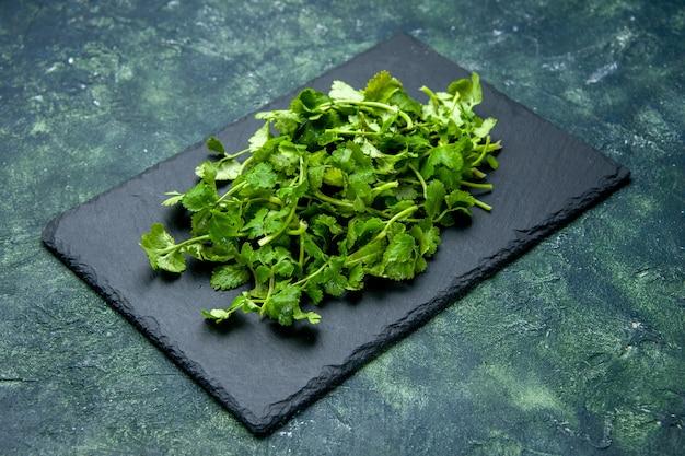 Vue latérale du paquet de coriandre sur une planche à découper en bois sur fond de couleurs mélangées noir vert avec espace libre