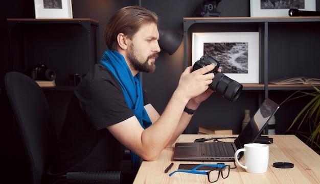 Vue latérale du photographe mature examinant les photos prises dans un appareil photo reflex numérique assis au bureau à la maison