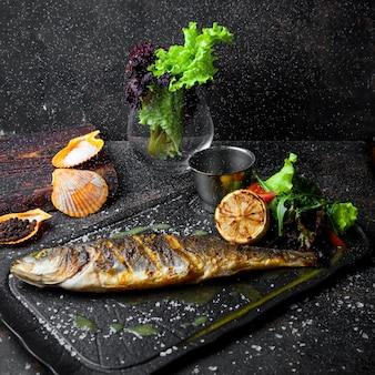 Vue latérale du poisson frit avec roquette et citron et tomate et sauce dans le bac