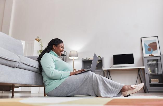 Vue latérale du portrait en pied d'une femme afro-américaine bien roulée souriant joyeusement et utilisant un ordinateur portable tout en profitant du travail à domicile assis sur le sol dans un intérieur minimal moderne, espace pour copie