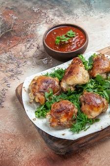 Vue latérale du poulet au poulet aux herbes sur lavash à côté du bol de sauce