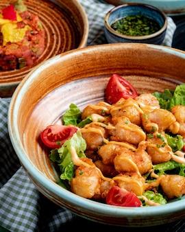 Vue latérale du poulet frit aux tomates et sauce sur la laitue sur une assiette sur rustique