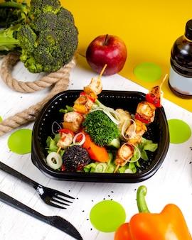 Vue latérale du poulet frit sur des brochettes de brocoli et d'oignons de légumes frais dans une boîte de livraison