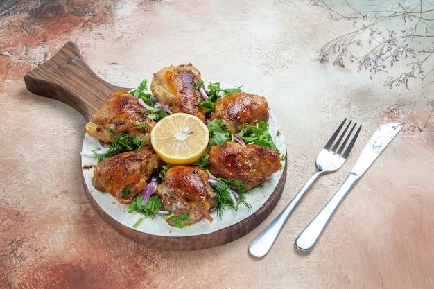 Vue latérale du poulet un poulet appétissant avec des herbes oignon citron sur le couteau et une fourchette