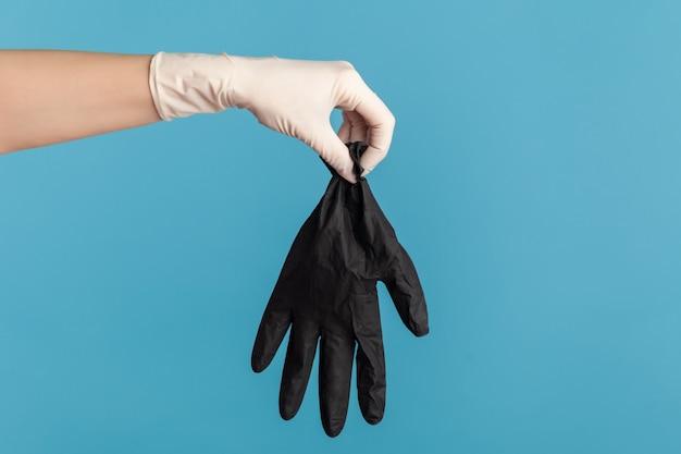 Vue latérale du profil agrandi de la main humaine dans des gants chirurgicaux blancs tenant des gants noirs.