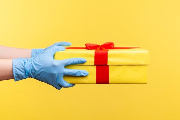 Vue latérale du profil agrandi de la main humaine dans des gants chirurgicaux bleus tenant une boîte-cadeau jaune.