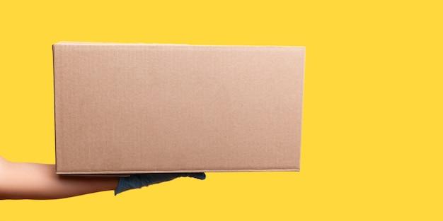 Vue latérale du profil agrandi de la main humaine dans des gants chirurgicaux bleus tenant la boîte. concept de livraison.