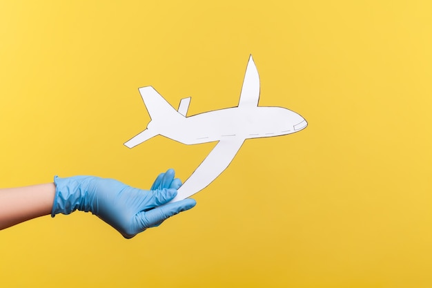Vue latérale du profil agrandi de la main humaine dans des gants chirurgicaux bleus tenant du papier d'avion.