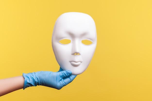 Vue latérale du profil agrandi de la main humaine dans des gants chirurgicaux bleus tenant un modèle de masque facial blanc.