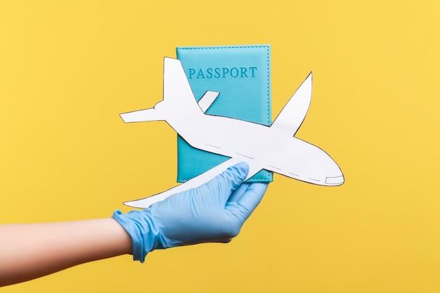 Vue latérale du profil agrandi de la main humaine dans des gants chirurgicaux bleus tenant un passeport et du papier d'avion.