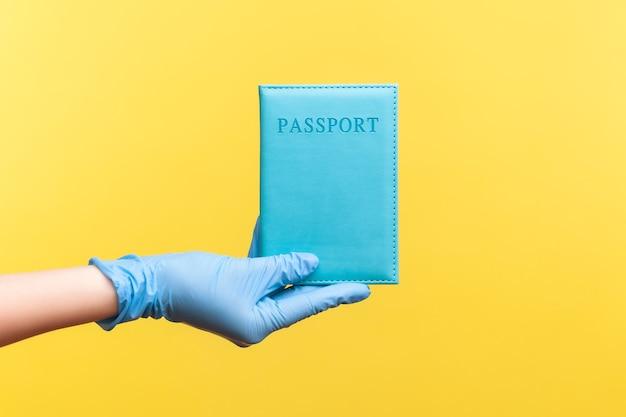 Vue latérale du profil agrandi de la main humaine dans des gants chirurgicaux bleus tenant un passeport à la main.