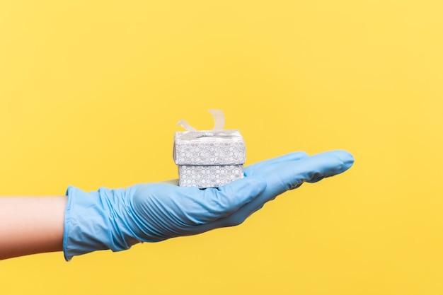 Vue latérale du profil agrandi de la main humaine dans des gants chirurgicaux bleus tenant une petite boîte-cadeau.