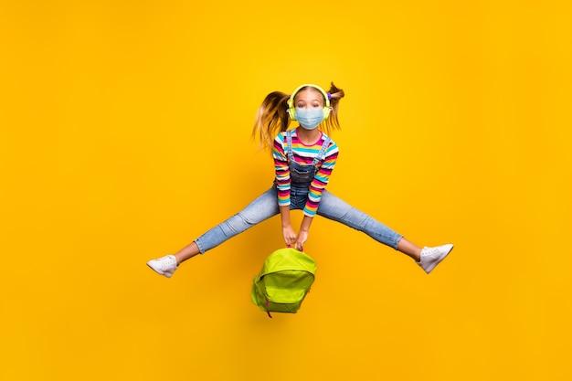 Vue latérale du profil complet du corps de sa belle fille séduisante sautant avec un masque de sécurité arrêter l'infection grippale grippe chine wuhan isolé fond de couleur jaune vif éclatant brillant