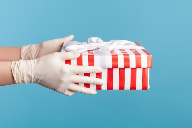 Vue latérale du profil en gros plan de la main humaine dans des gants chirurgicaux blancs tenant une boîte-cadeau rouge à rayures blanches.