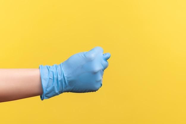 Vue latérale du profil en gros plan de la main humaine dans des gants chirurgicaux bleus montrant un geste.