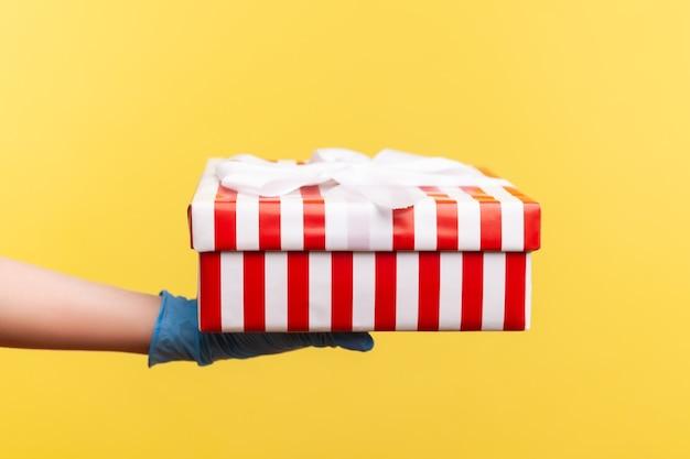 Vue latérale du profil en gros plan de la main humaine dans des gants chirurgicaux bleus tenant une boîte cadeau blanche à rayures rouges.