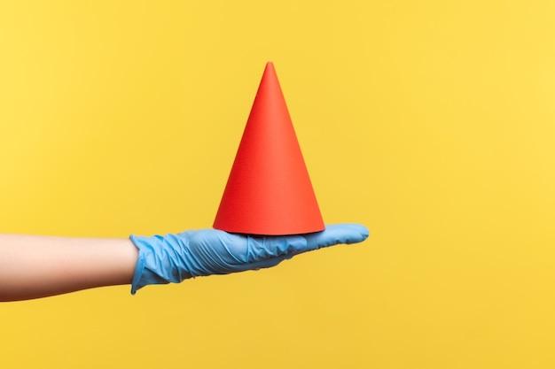 Vue latérale du profil gros plan de la main humaine dans des gants chirurgicaux bleus tenant un cône d'anniversaire rouge