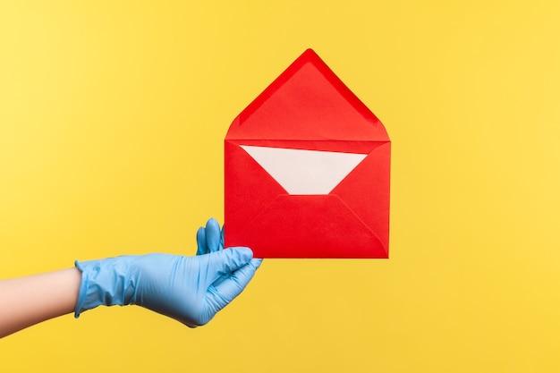 Vue latérale du profil en gros plan de la main humaine dans des gants chirurgicaux bleus tenant une enveloppe de lettre ouverte rouge.