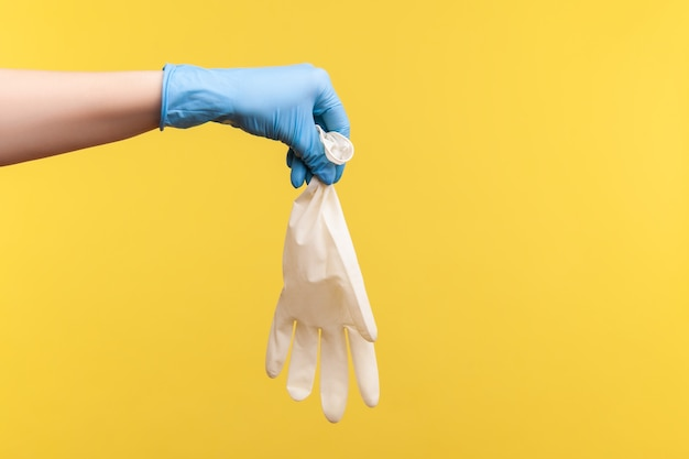 Vue latérale du profil gros plan de la main humaine dans des gants chirurgicaux bleus tenant des gants blancs