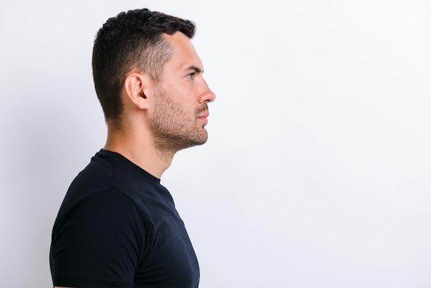 Vue latérale du profil portrait d'un beau jeune homme barbu calme et sérieux en chemise noire debout et impatient. studio intérieur tourné isolé sur fond de mur blanc clair