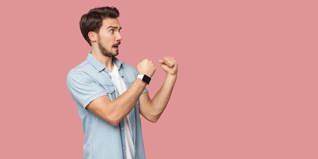 Vue latérale du profil portrait d'un beau jeune homme barbu en colère en chemise de style décontracté bleu debout, impatient dans les poings de boxe et prêt à attaquer. tourné en studio intérieur, isolé sur fond rose