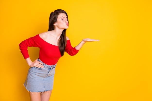 Vue latérale du profil portrait d'elle elle belle jolie fille adorable et rêveuse magnifique envoyant un baiser d'air 14 février cadeau espace de copie présent isolé sur fond de couleur jaune vif brillant éclatant