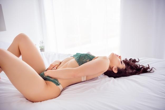 Vue latérale du profil portrait d'elle, elle s'adapte bien, mince, séduisante, chic, superbe fille allongée sur du lin se câlinant elle-même profitant de la joie dans un appartement intérieur blanc clair