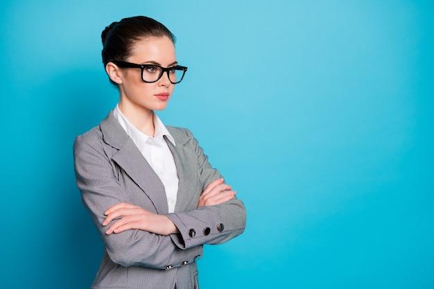 Vue latérale du profil portrait d'un employé de dame intelligente qualifié, calme et élégant, les bras croisés isolés sur fond de couleur bleu vif