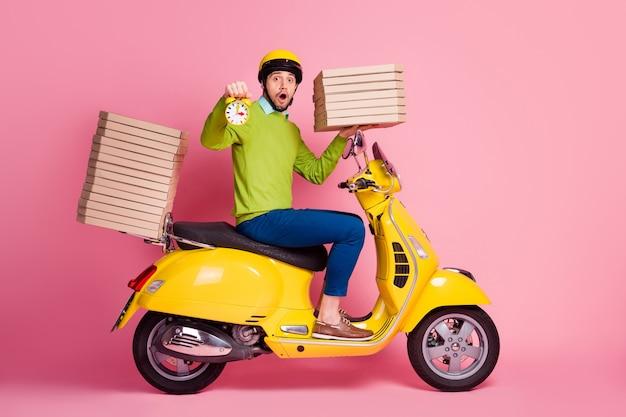 Vue latérale du profil portrait de gars conduisant un cyclomoteur tenir horloge boîtes à pizza pile