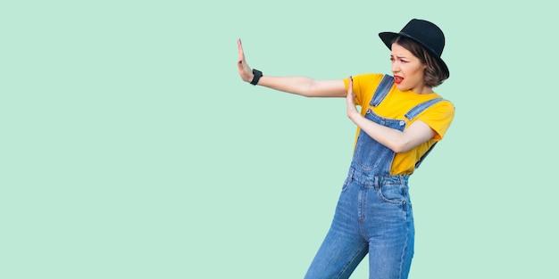 Vue latérale du profil portrait d'une jeune fille hipster effrayée en salopette en jean bleu, chemise jaune et chapeau noir debout avec un geste de signe de main d'arrêt. studio intérieur tourné isolé sur fond vert clair.