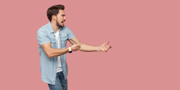 Vue latérale du profil portrait d'un jeune homme barbu criant grave en chemise décontractée bleue debout en attaque ou en tirant le geste des mains et regardant vers l'avant. tourné en studio intérieur, isolé sur fond rose.