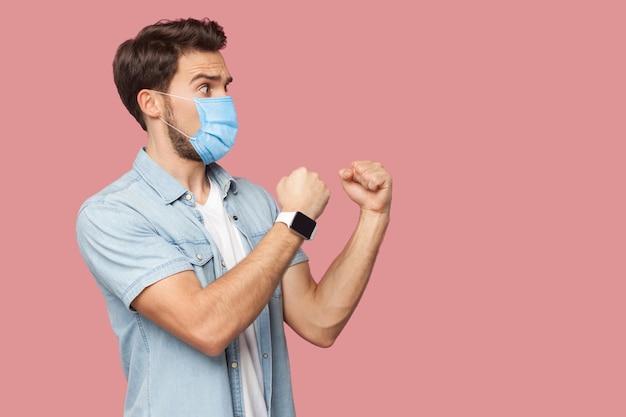 Vue latérale du profil portrait d'un jeune homme en colère avec un masque médical chirurgical en chemise bleue debout, impatient dans les poings de boxe et prêt à attaquer. tourné en studio intérieur, isolé sur fond rose