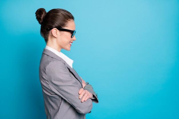 Vue latérale du profil portrait d'une jolie dame intelligente joyeuse assistante les bras croisés isolés sur fond de couleur bleu vif