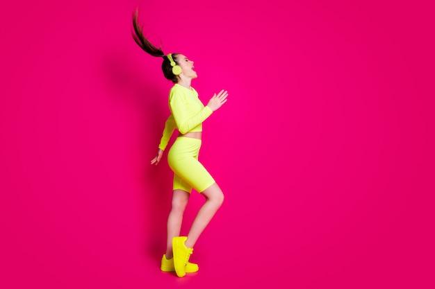 Vue latérale du profil de la taille du corps sur toute la longueur d'elle, elle séduisante fille mince et joyeuse écoutant de la musique pop rock s'amusant à danser isolé sur fond de couleur rose fuchsia brillant vif éclatant