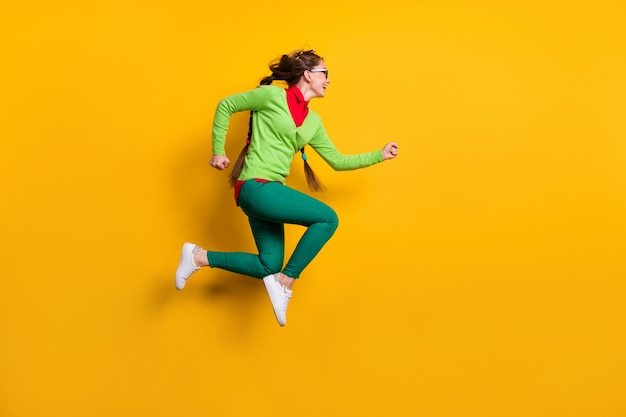 Vue latérale du profil de la taille du corps sur toute la longueur d'une fille joyeuse et énergique assez funky sautant en cours d'exécution sur fond de couleur jaune vif isolé