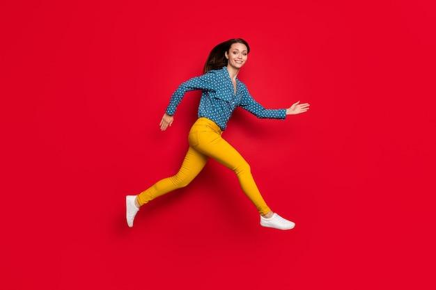 Vue latérale du profil de la taille du corps sur toute la longueur d'une fille motivée mince et gaie qui saute en courant isolée sur fond de couleur rouge vif