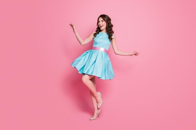 Vue latérale du profil de la taille du corps sur toute la longueur d'une fille s'amusant posant un fond de couleur rose isolé