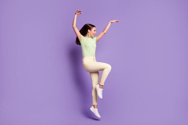 Vue latérale du profil de la taille du corps sur toute la longueur d'une jolie fille gaie et gaie sautant dans un mouvement moderne s'amusant isolé sur fond de couleur violet lilas vif éclatant éclatant
