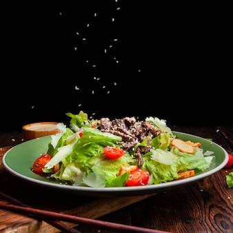 Vue latérale du riz coulant sur un délicieux repas de salade en plaque avec des baguettes sur fond en bois et noir. espace pour le texte