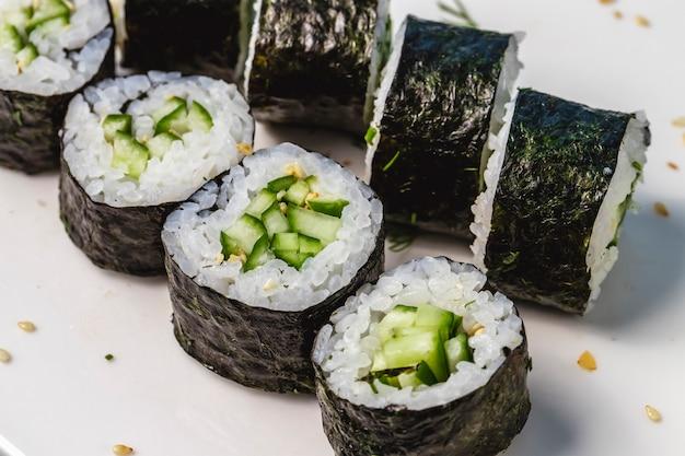 Vue latérale du riz kappa maki enveloppé d'algues et de concombre sur une plaque