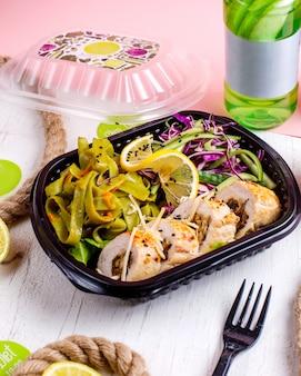 Vue latérale du rouleau de poulet farci à l'ail et aux noix de légumes servi avec une salade de chou dans la boîte de livraison