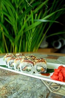 Vue latérale du rouleau de sushi cuisine japonaise traditionnelle avec anguille avocat et fromage à la crème sur vert