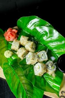 Vue latérale du rouleau de sushi de cuisine japonaise traditionnelle avec du thon servi avec du gingembre sur feuille verte